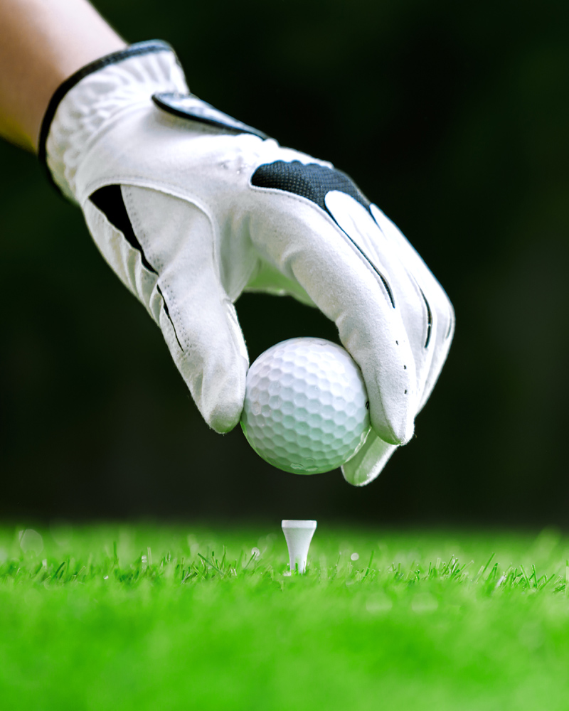 Hand putting golf ball on tee in golf course